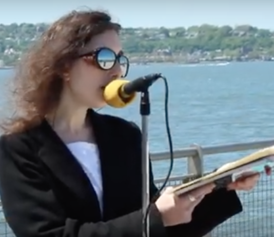 Lady recites poetry in celebration of Walt Whitman's 200th Birthday alongside New York Harbor.